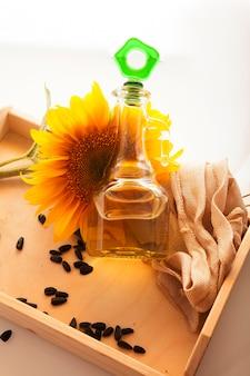 Olio di girasole in brocca trasparente con fiore di girasole