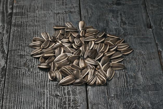 I semi di girasole sono sparsi su un tavolo di legno nero. la fresca resa del girasole.