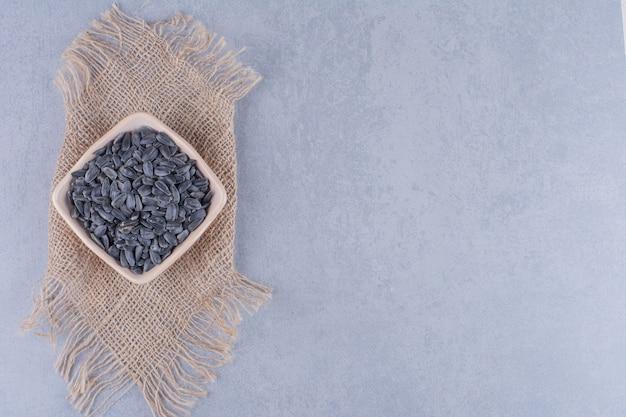 Semi di girasole in una ciotola su un tovagliolo di tela da imballaggio sulla superficie di marmo