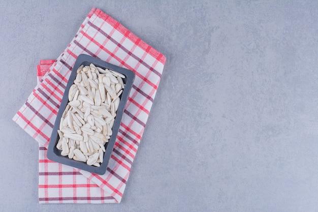 Semi di girasole in un piatto di legno su un canovaccio sulla superficie di marmo