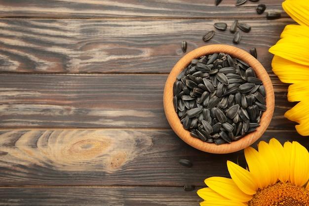 Girasole con semi in ciotola su fondo di legno marrone