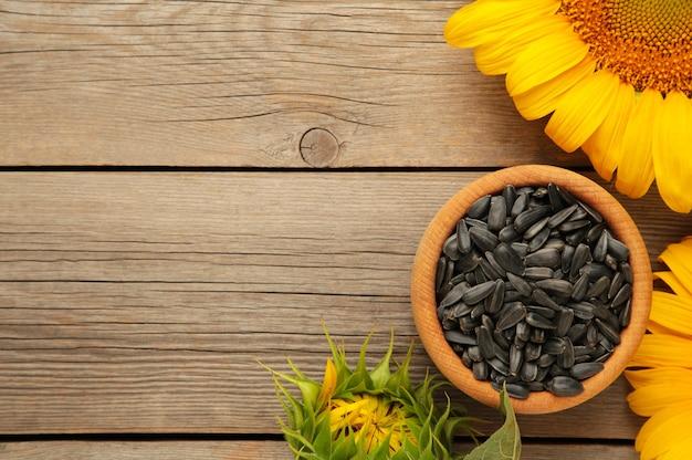 Girasole con semi in ciotola su fondo di legno grigio. vista dall'alto