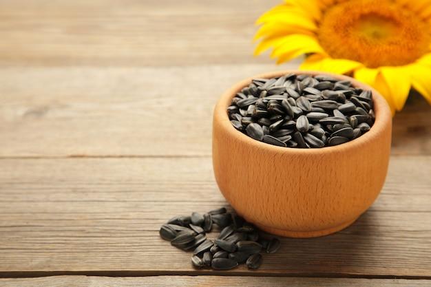 Girasole con semi in ciotola su fondo di legno grigio
