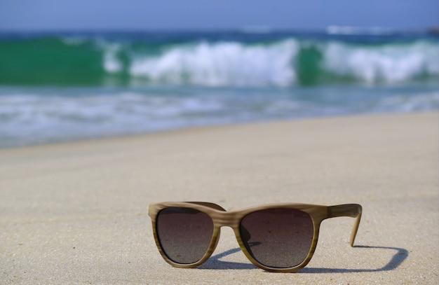 Occhiali da sole sulla spiaggia con onde schizzi sfocate