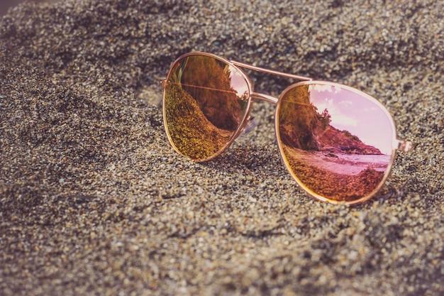 Occhiali da sole in spiaggia con riflesso del mare.