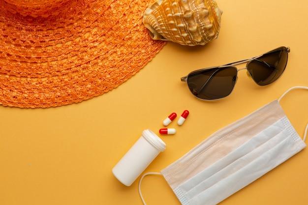 Occhiali da sole e cappello su sfondo arancione con maschera protettiva il concetto di vacanze pandemiche