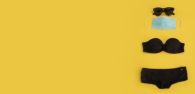 Maschera medica per occhiali da sole e bikini nero su sfondo giallo spazio libero per lo spazio della copia del testo