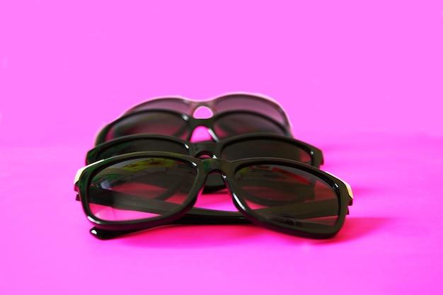 Occhiali da sole su sfondo rosa pastello. occhiali con montatura nera. accessori moda per la protezione dai raggi uv degli occhi.