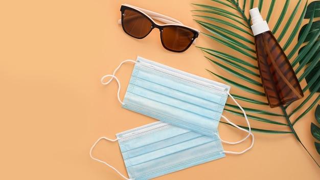 Occhiali da sole, crema protettiva spf, mascherine mediche. accessorio da spiaggia. viaggio estivo nel concetto di quarantena del coronavirus