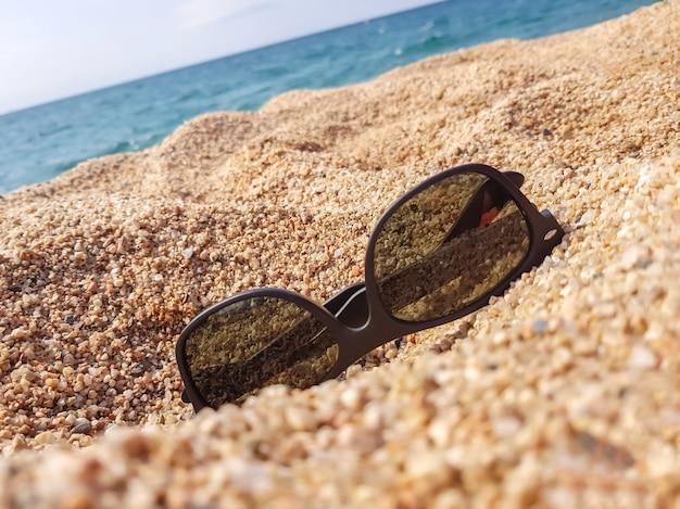 Occhiali da sole sulla spiaggia di sabbia
