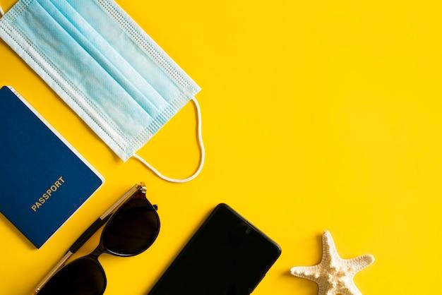 Occhiali da sole, stelle marine e conchiglie, passaporto, maschera e disinfettante sul giallo