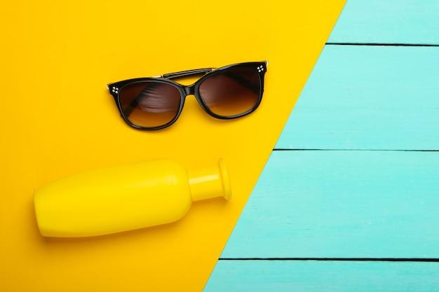 Occhiali da sole, bottiglia di protezione solare su un blu di legno
