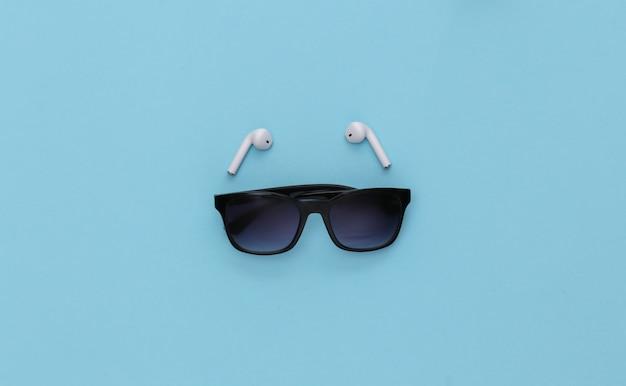 Occhiali da sole e auricolari wireless su sfondo blu.