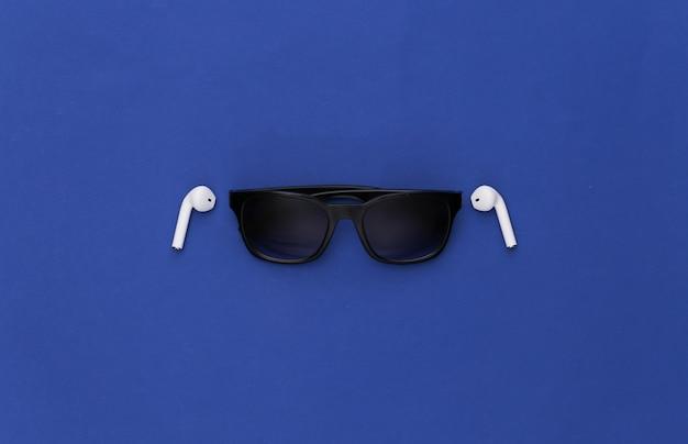 Occhiali da sole e auricolari wireless su sfondo blu classico.