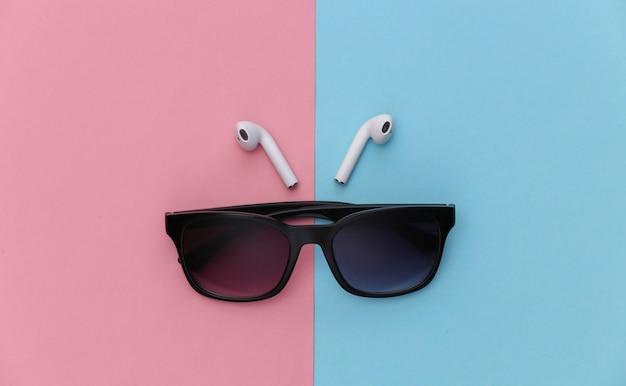 Occhiali da sole e auricolari wireless su sfondo rosa pastello blu.