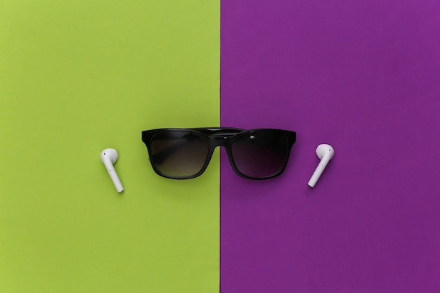 Occhiali da sole e auricolari wireless su uno sfondo viola-verde.