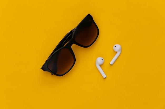 Occhiali da sole e auricolari wireless su sfondo giallo.