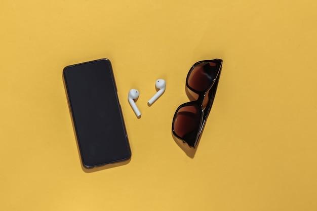 Occhiali da sole, cuffie wireless e smartphone su uno sfondo giallo brillante.