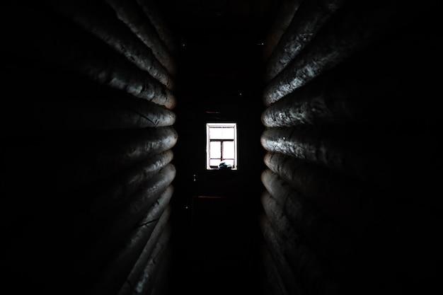 La luce del sole che entra dalla finestra di legno in una vecchia stanza buia