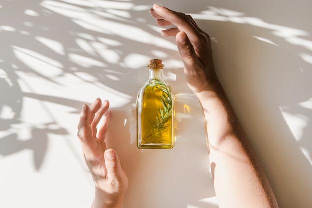 Luce solare che cade sopra le mani che coprono la bottiglia di olio su fondo bianco