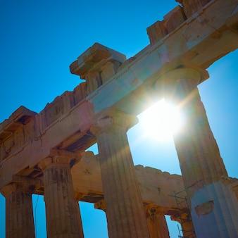 La luce del sole penetra attraverso le antiche colonne di un tempio ad atene, in grecia
