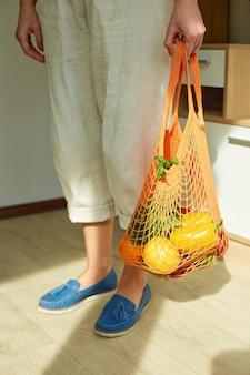 Luce solare con vista dall'alto della donna in scarpe verdi che tiene la borsa a rete riutilizzabile della drogheria di stringa piena di frutta fresca e verdura a casa concetto di shopping e alimentazione sana vegana zero rifiuti
