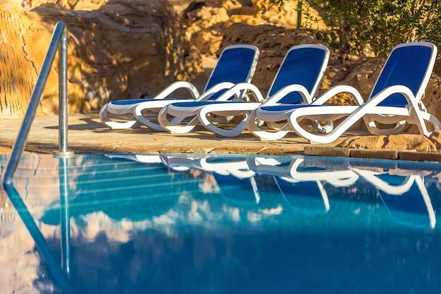 Lettini vicino alla piscina e si riflettono nell'acqua blu