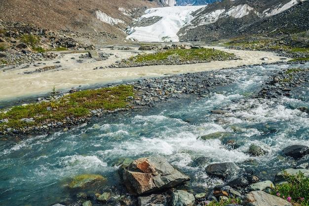 Paesaggio alpino soleggiato con confluenza di due diversi fiumi di montagna. il bellissimo torrente chiaro sfocia nel fiume sporco. paesaggio montano colorato con confluenza di due fiumi diversi tra una ricca flora.