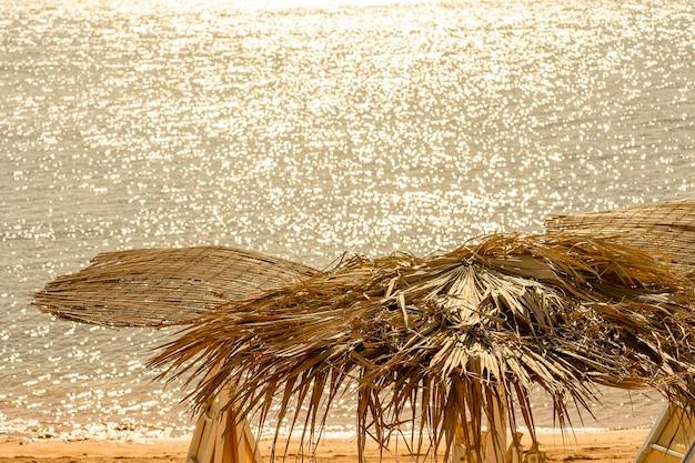 Sunny beach in controluce con ombrelloni di paglia concetto di vacanza e relax al tramonto
