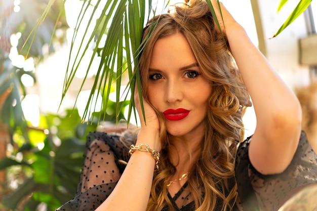 Soleggiato ritratto ravvicinato di una giovane donna riccia in posa vicino al giardino d'inverno con foglie tropicali, abito da sera glamour e trucco.