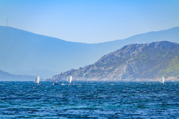 Giornata di sole nella baia estiva tra le montagne. tre piccoli yacht sportivi e un pullman su una barca a motore