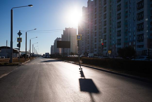 Mattinata di sole in città, edifici residenziali e strade vuote.