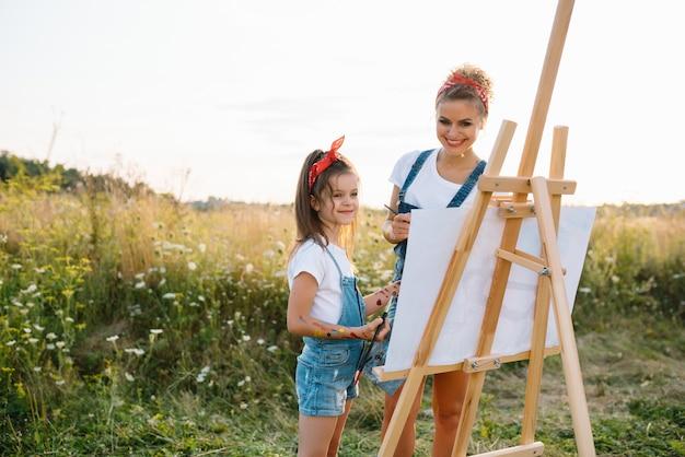 Natura soleggiata, mamma e figlia dipingono un quadro in un parco, dipingendo un bambino piccolo, creatività infantile.