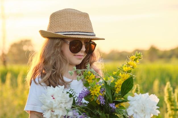 Ritratto esterno soleggiato della ragazza in cappello e occhiali da sole che tengono il mazzo di fiori in prato