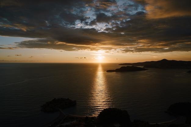 Percorso soleggiato sull'acqua dal tramonto nel cielo blu tra nuvole e nuvole in montenegro vicino al