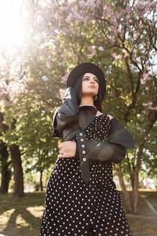 Ritratto soleggiato donna splendida in abito elegante nero in cappello alla moda in giacca di pelle vintage nel parco in una giornata di sole luminoso. bella bella ragazza castana e luce solare sulla natura in primavera.