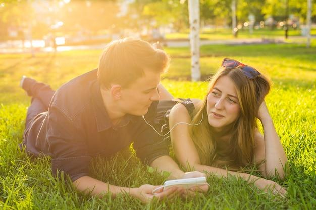 Ritratto soleggiato di dolce giovane coppia sdraiata rilassante sull'erba insieme ascolta musica in auricolari su smartphone, giorno d'estate.