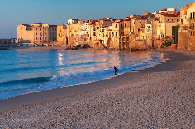 Spiaggia di sabbia soleggiata nel centro storico della città costiera di cefalù al tramonto, sicilia, italia
