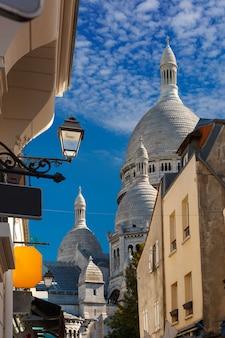 Sunny street e le cupole del sacre-coeur al mattino, quartiere montmartre a parigi, francia