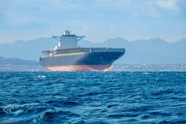 Giornata di sole estivo e mare calmo. nave da carico vuota vicino alla costa mediterranea