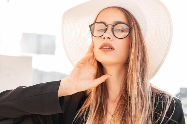Soleggiato ritratto estivo carino giovane donna con belle labbra in occhiali alla moda con capelli lunghi in elegante giacca nera con cappello di paglia bianco vintage in una luminosa giornata di sole. ragazza attraente e luce solare.