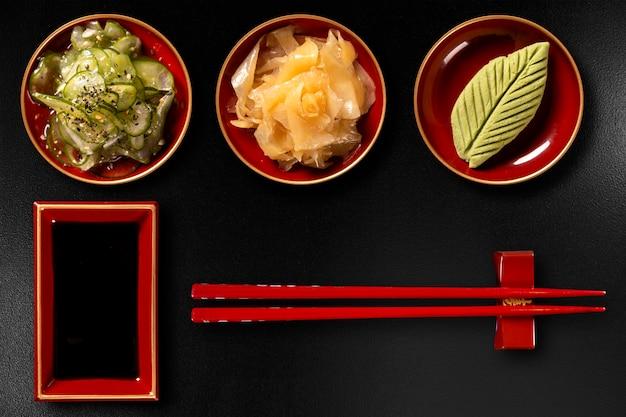 Sunomono, zenzero, wasabi, hashi e shoyu isolati su sfondo nero. vista dall'alto.