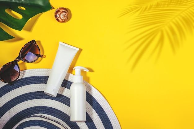 Oggetti di protezione solare. cappello da donna con occhiali da sole e crema protettiva spf piatto giaceva su sfondo giallo. accessori da spiaggia. concetto di vacanza di viaggio estivo