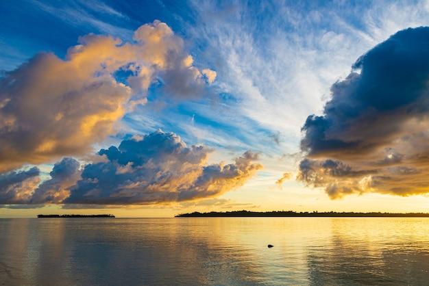 Cielo drammatico di alba sul mare, spiaggia tropicale del deserto, nuvole tempestose