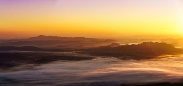 Alba sullo sfondo di montagne nebbiose.
