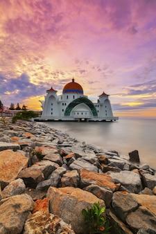 Momenti di alba alla moschea dello stretto di malacca (masjid selat melaka), è una moschea situata sull'isola artificiale di malacca vicino alla città di malacca, in malesia