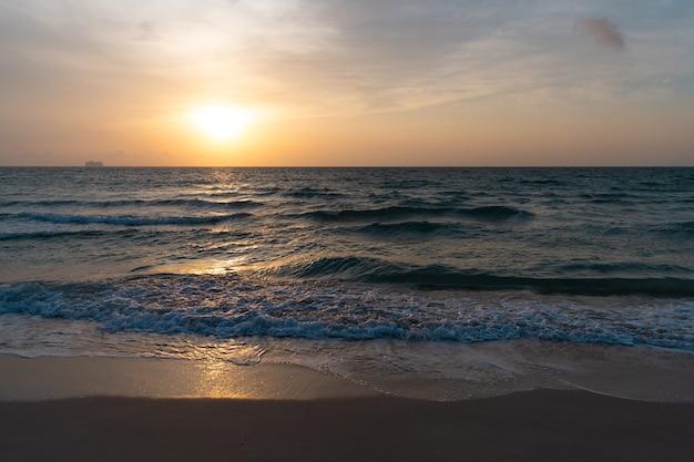 Alba nell'oceano o nell'acqua di mare a miami beach con la sagoma della nave sullo sfondo del cielo al tramonto