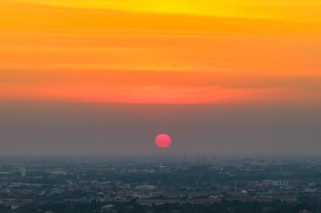Tramonto di alba nella città con il fuoco selettivo sul sole