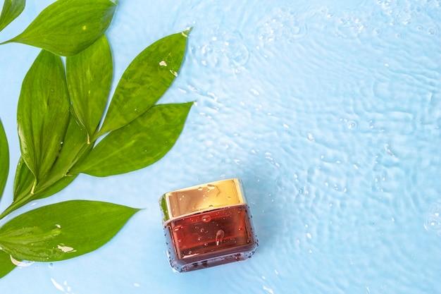 Crema solare con foglie verdi sulla superficie dell'acqua blu della piscina