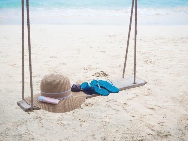 Scarpe cappello protezione solare su altalena con sfocatura immagine di sfondo blu del mare estate e concetto di vacanza